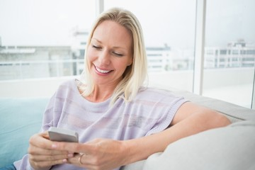 Woman text messaging through mobile phone in living room