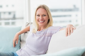 Smiling woman sitting on sofa in living room