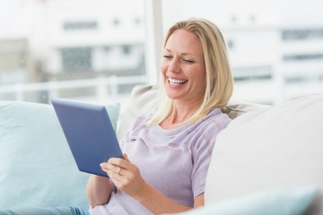 Cheerful woman using tablet computer on sofa