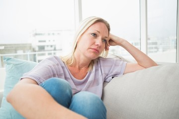 Sad woman sitting on sofa