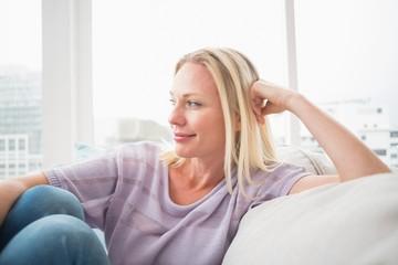 Thoughtful woman sitting on sofa