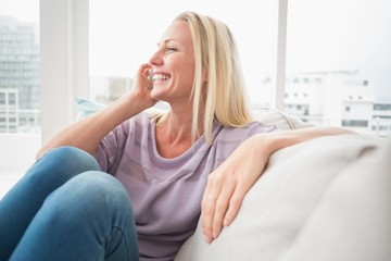 Smiling woman talking on mobile phone on sofa