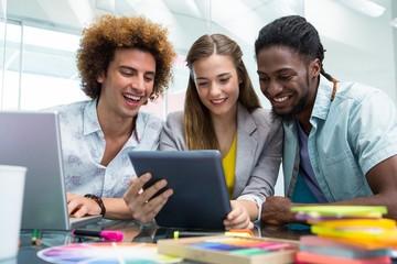 Creative business people looking at digital tablet