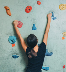 Sporty woman climbing up on rock wall indoor