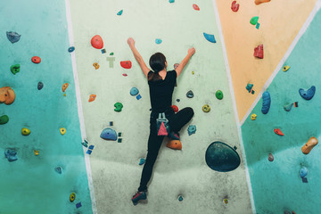 Sporty woman climbing up on practice rock wall indoor