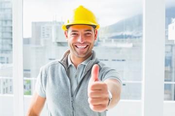 Manual worker gesturing thumbs up in building
