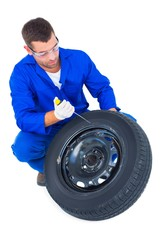 Mechanic working on tire over white background