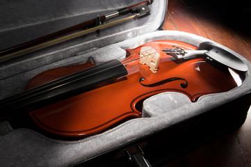 Wooden violin in black case.