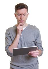 Denkender junger Mann mit Tablet Computer