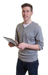 Stehender junger Mann mit Tablet Computer