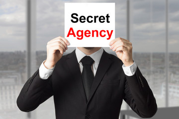 businessman hiding face behind sign secret agency