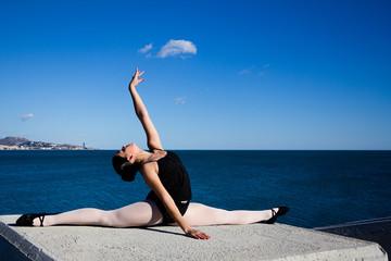 Danseuse faisant le grand écart en bord de mer.