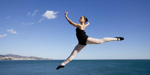 Danseuse suspendue en l'air dans un ciel bleu.