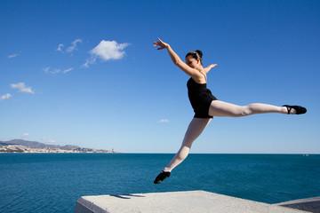 Gracieux saut d'une danseuse en bord de mer.