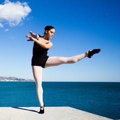 Danseuse levant la jambe au bord de la mer Méditerranée.
