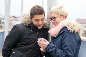 Young Woman and Man looking into Smartphone