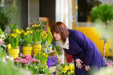 Beautiful woman selecting flowers at flower market