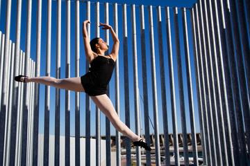 Saut dynamique d'une danseuse en ville.