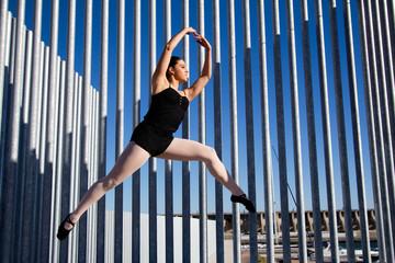 Saut d'une danseuse sur un fond de tubes métalliques.