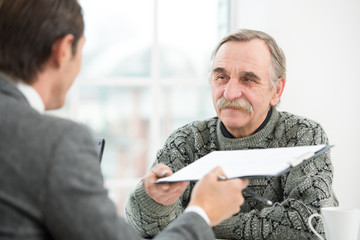 Businessman having an interview with smiling old man