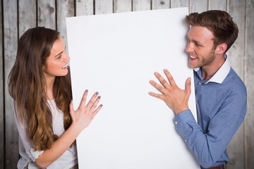Composite image of happy young couple with blank board