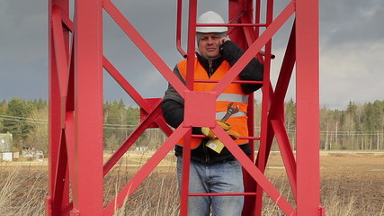 Worker with cell phone near metal structures