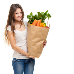 Woman holding a shopping bag full of fruit and vegetables