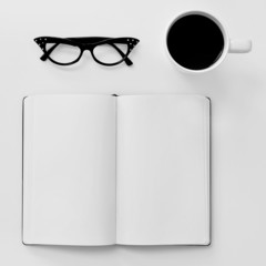 blank notebook, eyeglasses and cup of coffee on a white table