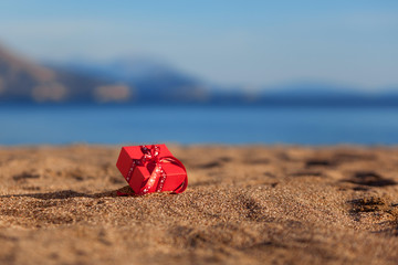 Red gift box on a beach