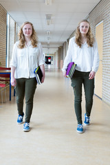 Two girls walking in long school corridor carrying text books