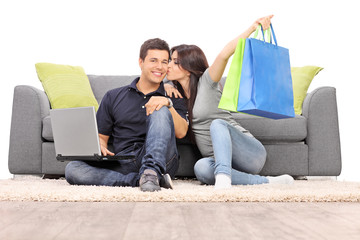 Woman with shopping bags kissing her boyfriend