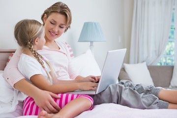 Mother and daughter using laptop in bed
