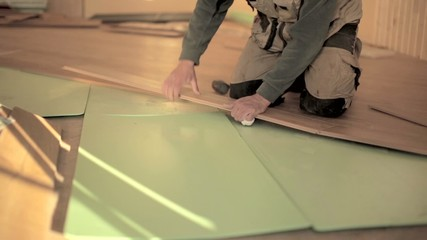 Builders man Install in construction house Laying Laminate Floor