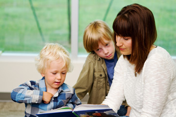 Mom reading a book to two children