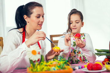 Little girl and mother coloring eggs for Easter