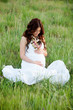 Relaxed pregnant woman sitting on the grass
