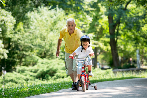 grandfather and child in park using tablet - 79261929