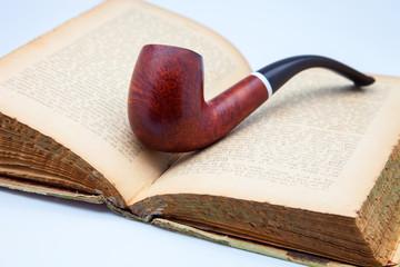 libro abierto y pipa de tabaco