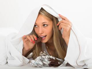Woman eating  chocolate  in bed