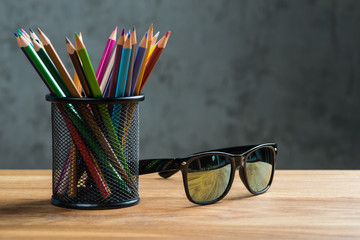 Black sun glasses with bunch of color pencils in a stand