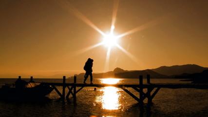 Playful Couple On Bridge At Sunset