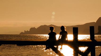 Two Children Sitting On Bridge At Sunset