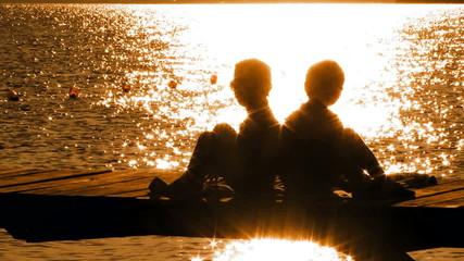 Little Boy and Girl Sitting On Bridge At Sunset