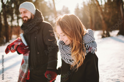 Young hipster couple walking in winter forest holding hands - 79262760