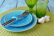 Empty colorful plate, glasses and silverware set on wooden