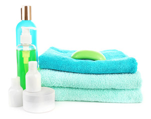 Stack of towels with shampoo bottles and soap isolated on white