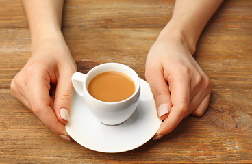 Female hands holding cup of coffee on wooden planks background