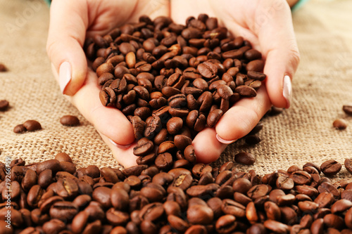 Female hands with coffee beans in shape of heart
