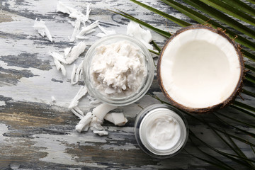 Coconut with coconut oil in bowl with jar of cosmetic cream