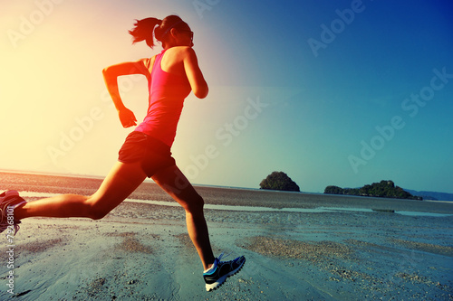 canvas print picture young woman running on sunrise beach